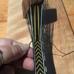 This loop is held down (towards the weaving) to prevent any funny loops/twists while the weft thread is pulled taut. Pull until the loop is gone and the band is compact. Don't pull too tight or your band width will vary.