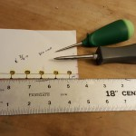 Eyelet template next to old awl (top) and new awl (bottom).
